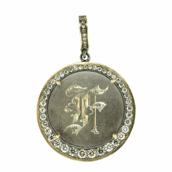 "Closeup photo of Love Token Engraved With ""F"""