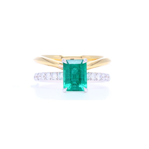 Closeup photo of 18k Yellow Gold Emerald Cut Zambian Emerald Ring with Split Diamond Shank Band
