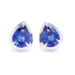 Closeup photo of Pear Shaped Blue Sapphire Bezel Set Studs in 18k White gold